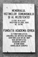 Placa explicativă - Memorialul victimelor comunismului şi al rezistenţei a fost realizat începând cu anul 1993 de către Fundaţia Academia Civică şi funcţionează ca autoritate de interes naţional conform legii nr. 95.1997 sub autoritatea Academiei Civice şi sub egida Consiliului Europei